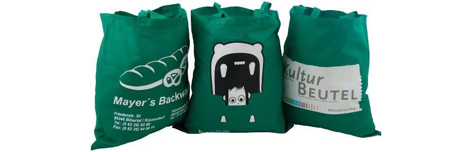 Ein Bild mit grünen Baumwolltaschen mit zwei kurzen Henkeln, mehrfarbig bedruckt