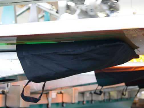 Hier ist zu sehen, wie eine schwarze Baumwolltasche auf eine Druckpalette aufgezogen ist