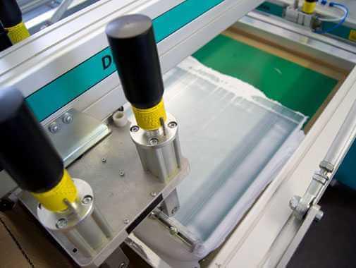 Ansicht einer Druckschablone, mit der die Druckfarbe mittels eines Rakel auf die Stofftasche gedrückt wird